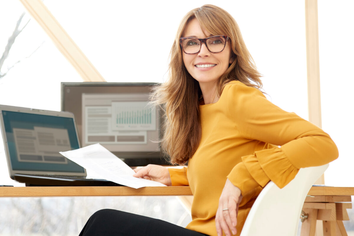 Smiling mature businesswoman using a laptop and computer in an office