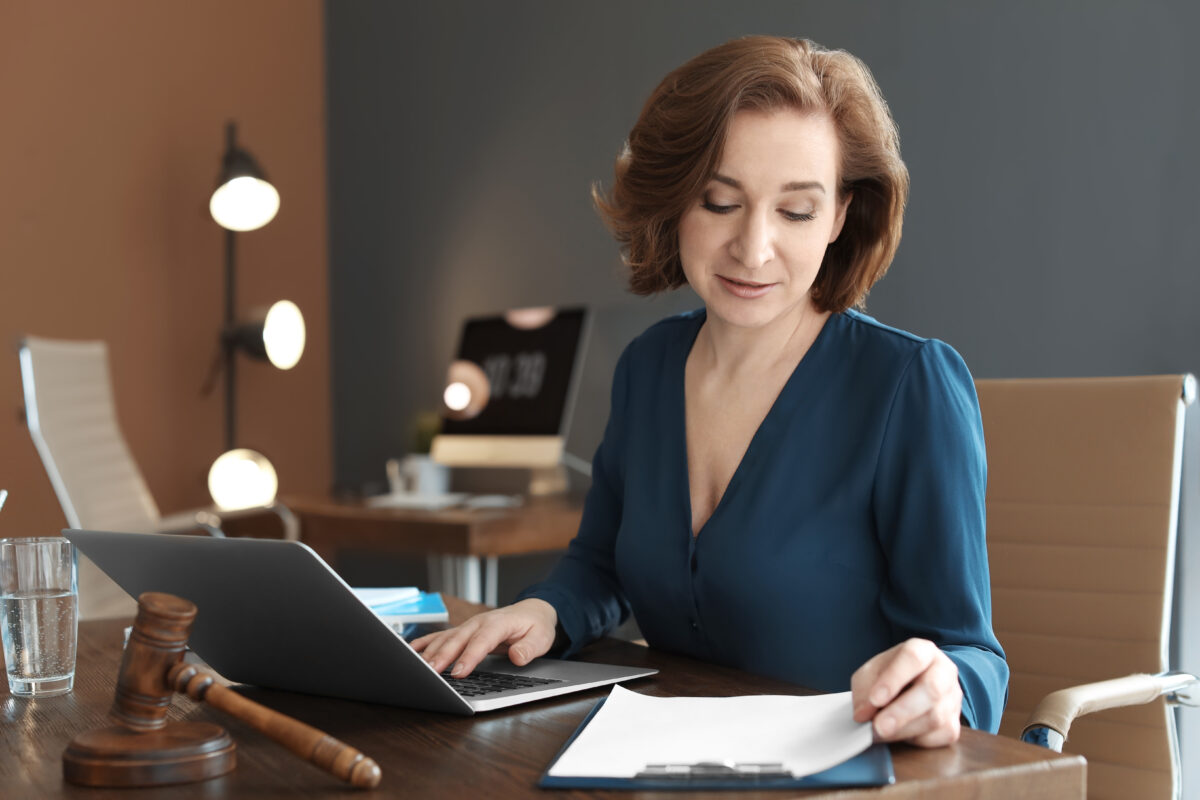 Smiling mature lawyer reading documents while using a laptop in an office