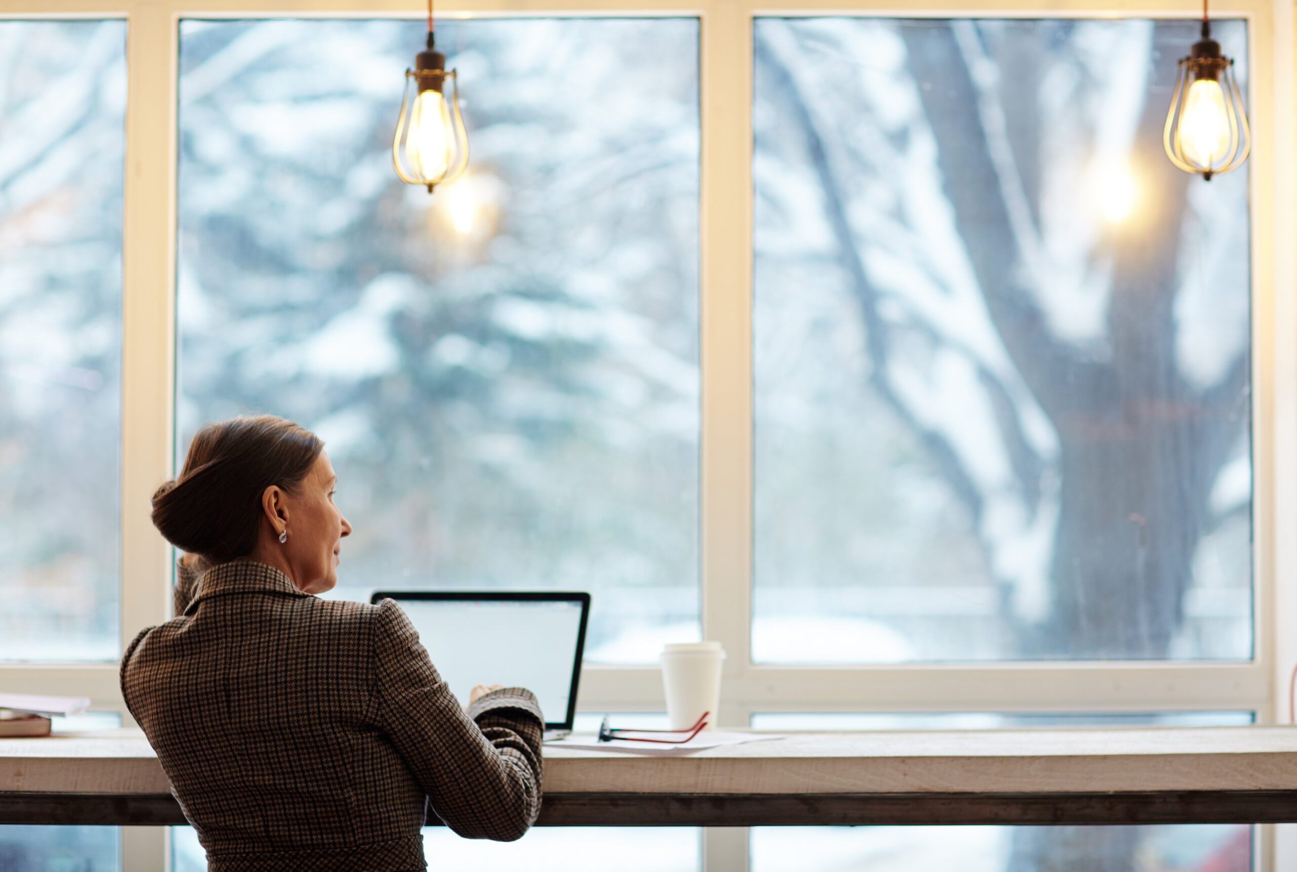 Woman looking out the window while seated by a long table working on a laptop