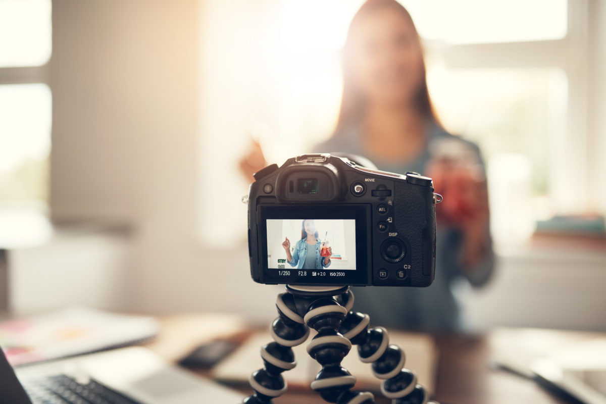Young woman making a vlog holding refreshing drink and smiling.